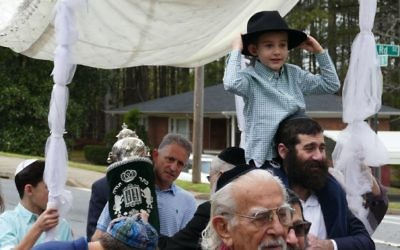 In front of the Torah and the chuppah, Noah Pawliger carries a living wonder along Lower Roswell Road.