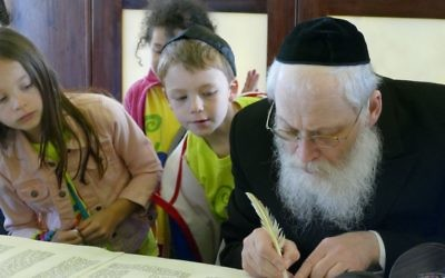 Cobb Hebrew School students closely watch sofer Rabbi Moshe Klein at work.