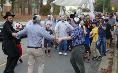 Rabbi Ephraim Silverman and Mitchell Kopelman are among those dancing in the street to celebrate the new Torah.