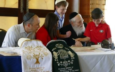 Rabbi Moshe Klein gets some help with one of the final letters of the Torah.