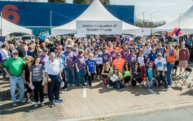 Photo courtesy of Federation Atlanta Community Food Bank President and CEO Kyle Waide (kneeling, in orange) joins the Jewish community's Hunger Walk/Run participants in front of the Federation tent in March 2017.
