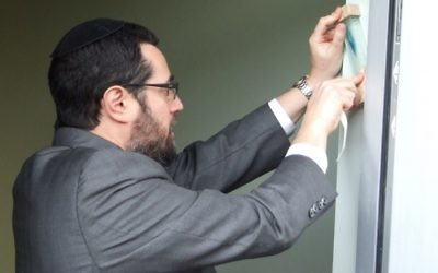 Rabbi Joshua Heller, one of the two honorees March 16, hangs the MACoM mezuzah at the opening ceremony in November 2015.