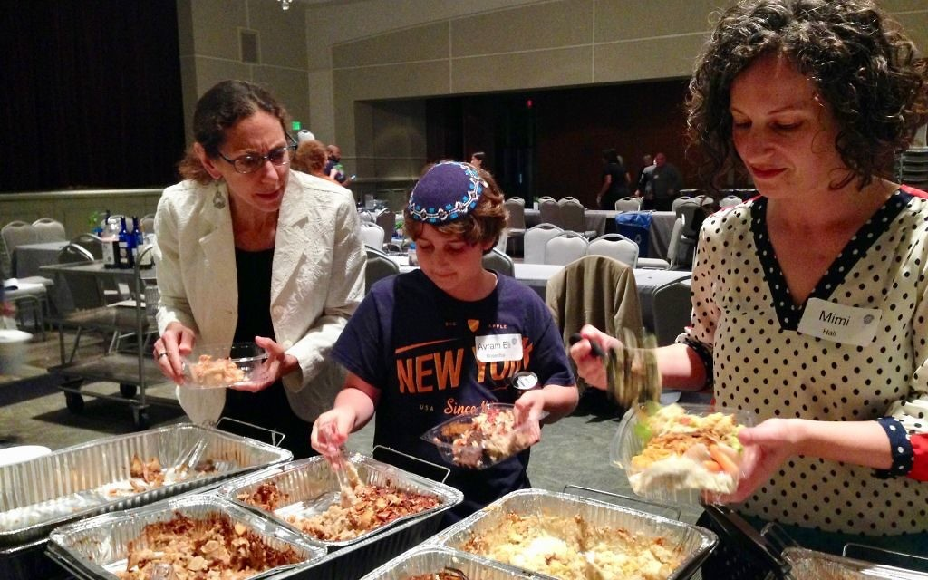 Audrey Galex, Avram Eli Rosenthal and Mimi Hall package individual meals for distribution after the 2016 Hunger Seder.