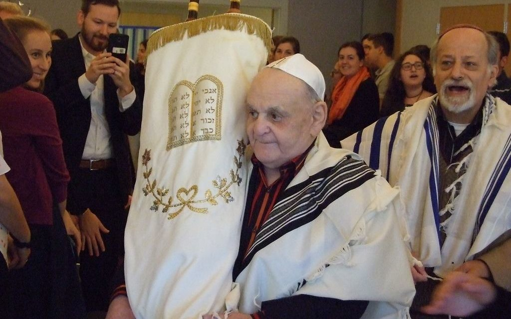 Bar mitzvah man Leon Asner carries the Torah before his first aliyah.