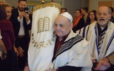 Bar mitzvah man Leon Asner carries the Torah before his first aliyah.