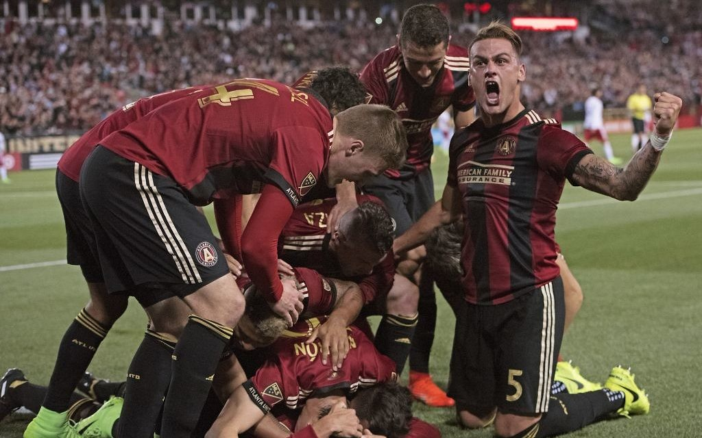 Atlanta United players celebrate the historic opening goal by Yamil Asad against the New York Red Bulls.