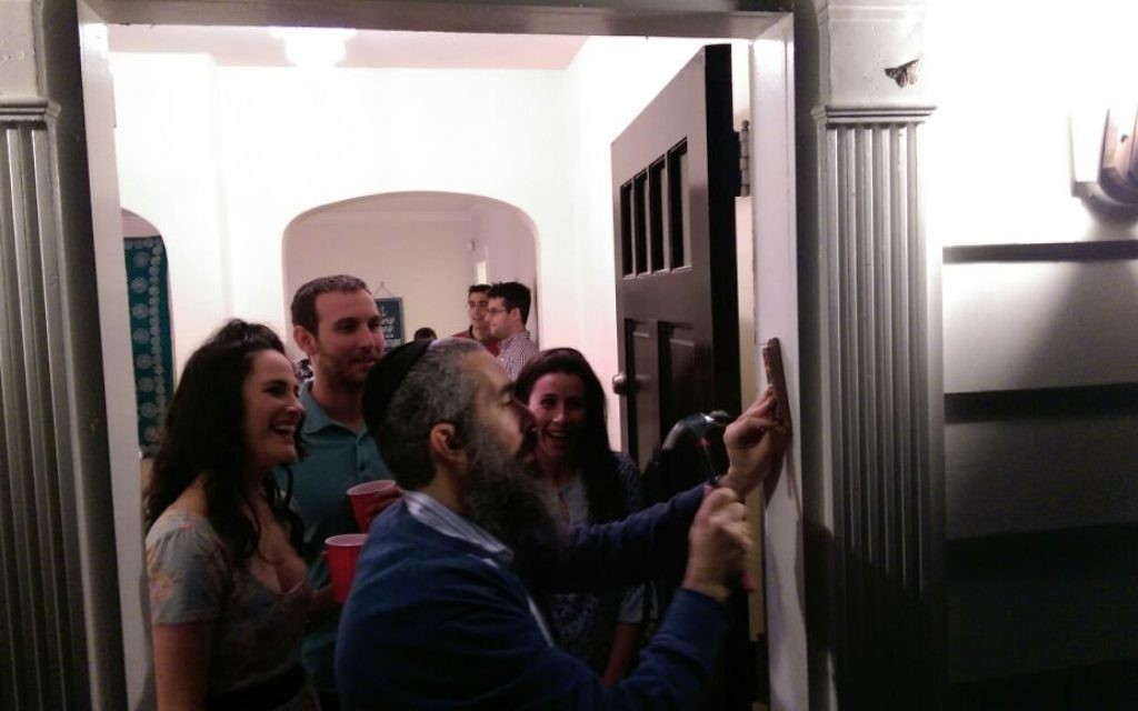 Moishe House residents Aviva Leigh, Matt Spruchman and Cassidy Artz watch as Rabbi Eliyahu Schusterman installs a mezuzah at the front door of the Buckhead house April 6.