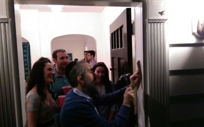 Moishe House residents Aviva Leigh, Matt Spruchman and Cassidy Artz watch as Rabbi Eliyahu Schusterman installs a mezuzah at the front door of the Buckhead house April 6.