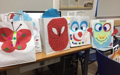 Students and mission participants prepare Purim gift bags for children hospitalized in Tiberias.