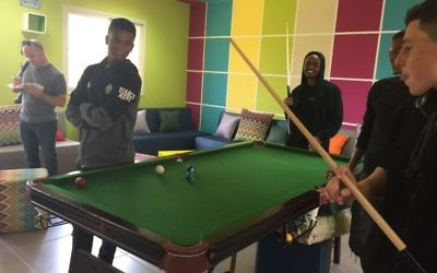 Students play pool in the student lounge, renovated with donations from Atlanta.