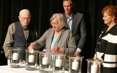 After receiving the helper candle from Marlene Besser, survivor Erica Lauten lights the fifth of six candles at the JCC ceremony with the help of Bernie Gross.