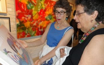Flora Rosefsky (right) discusses one of her pieces at the Different Trains Gallery opening. (Photo by Kevin C. Madigan)