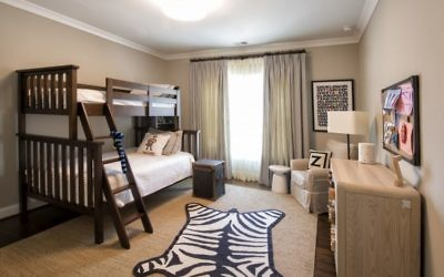 The young gentleman's room has space to play on this Jonathan Adler faux zebra rug. The adjoining bathroom features Schumacher's New York New York wallpaper