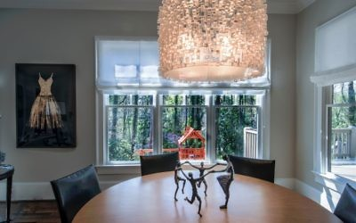 The breakfast room features a table and chairs from Crate & Barrel and the free-spirited dancer sculpture beneath an Ironies chandelier from Jerry Pair. The playground can be seen through the back window.