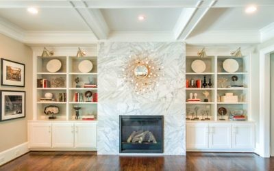 Beth Brown designed the shelves in the living room with a grass-cloth background around a concave starburst mirror.