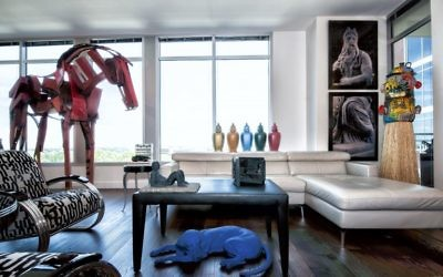 "The living room is home to Brooklyn-based KAWS' ""Astro Boy,"" a 2013 work in painted cast vinyl, and Louise Nevelson's untitled 1978 monochromatic wood construction box on the table; Sandy Skoglund's purple dog from ""Green House,"" a 1990 cast polyester resin, under the table; Allan McCollum's 1987 ""Perfect Vessels"" in the background; Andres Serrano's ""Gray Moses,"" a Cibachrome photograph from 1990; and Michael Lucero's ""Double Jug Head,"" made of ceramic and straw in 1994."