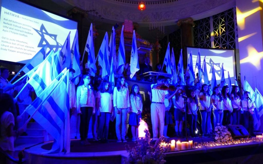 """While members of the Israeli Scouts and B'nei Akiva hold Israeli flags, Epstein School student Joshua Sampson plays the violin to lead the singing of """"Hatikva"""" at the end of the Yom HaZikaron ceremony April 30 at The Temple."""