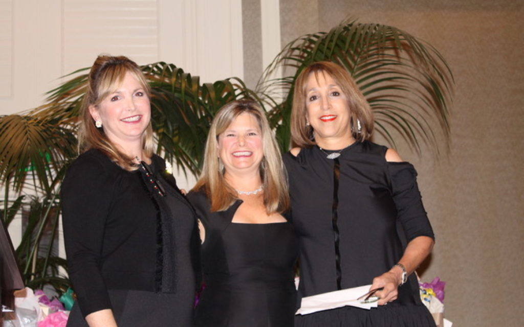 All coordinated in black, Brooke Blasberg (left) passes the chair's gavel to Jodie Jackson (center) and Sharon Corenblum (right).