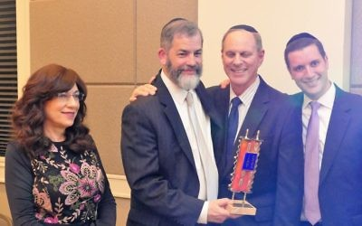 Rabbi Ilan Feldman accepts the Beth Jacob award on behalf of his wife, Miriam, from synagogue Vice President Cliff Alsberg and President Josh Joel (right).