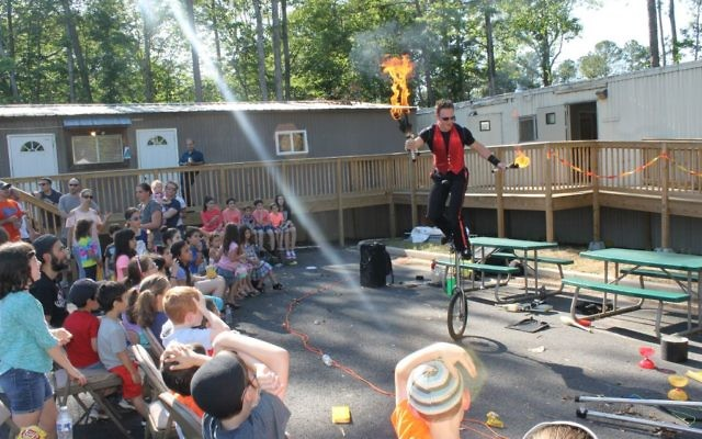 Rather than a bonfire, one man on a unicycle handles the flames.