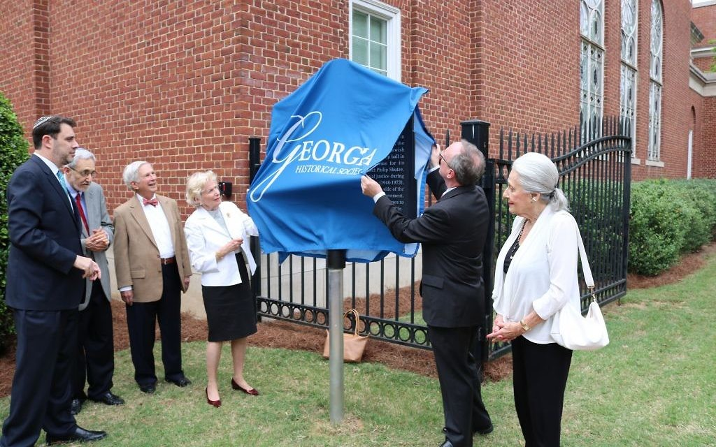W. Todd Groce uncovers the historical marker in front of (from left) Senior Rabbi Peter Berg, Rabbi Emeritus Alvin Sugarman, Tony and Jackie Montag, and Janice Rothschild Blumberg.