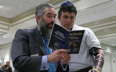 Rabbi Eliyahu Schusterman helps Josh Pastner wrap tefillin after the Jewish Business Network-Midtown breakfast May 10, 2017.