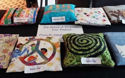 "Pillows created by Peach State Stitchers for a convention challenge reflect the theme of ""We Have a Dream for Peace."""