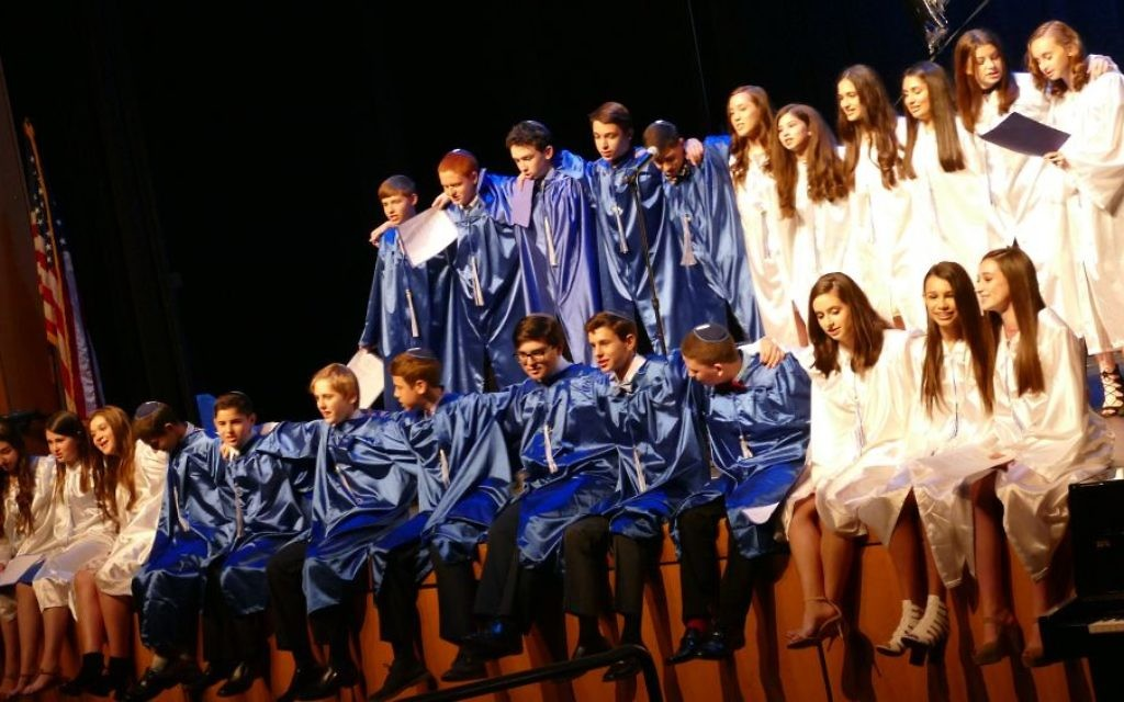 The 24 members of the eighth-grade Class of 2017 sing together for the last time at the end of their recognition ceremony.