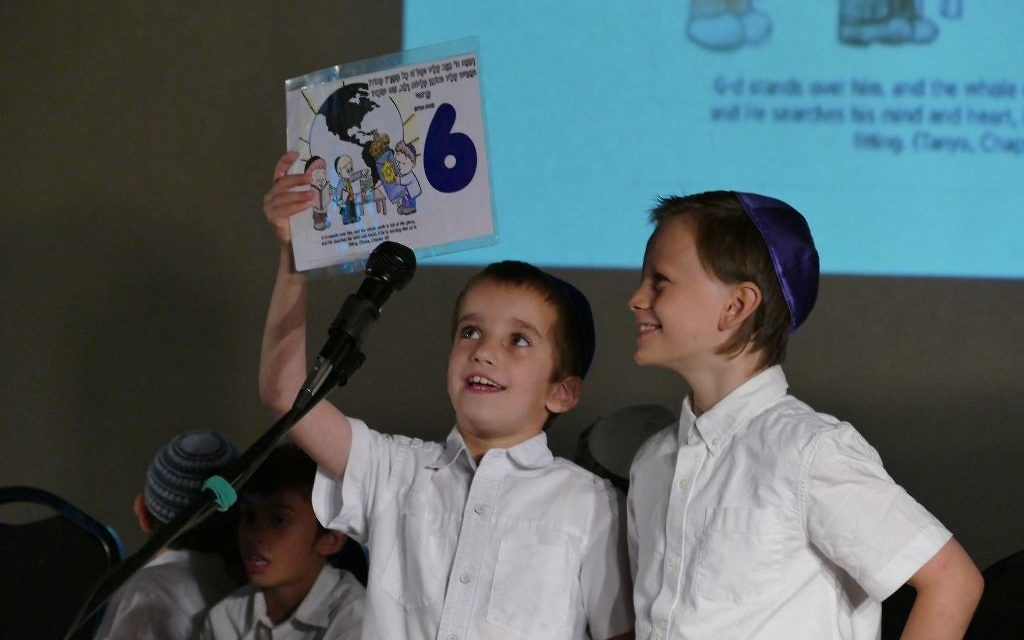 First- and second-graders hold up a sign during a song at the CMCH end-of-year event.
