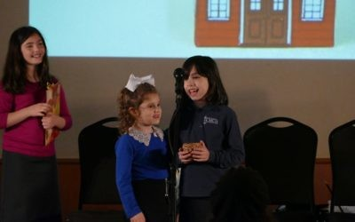 First- and second-grade girls have fun putting on a skit for the crowd.