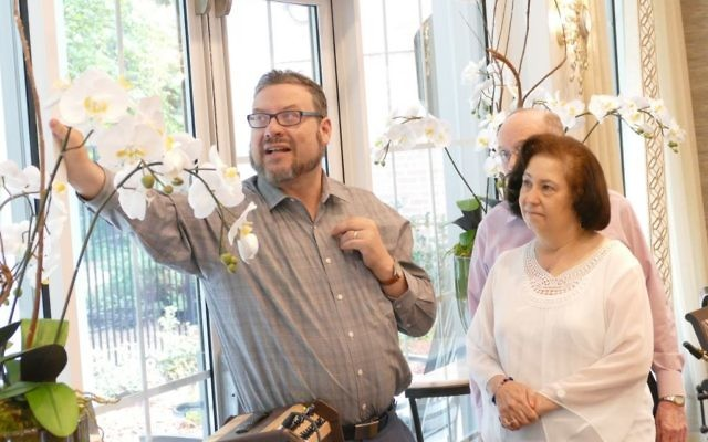 Congregation Gesher L'Torah Rabbi Michael Bernstein places and blesses one of two mezuzot around the dining room with the help of Cohen family members Lynda and Joel Schaffer.