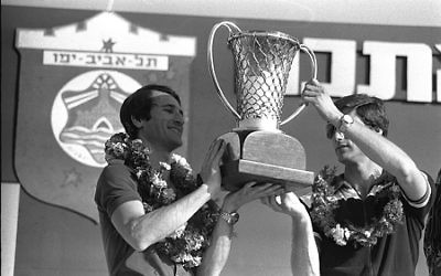 Yaacov Sa'ar, Israeli Government Press Office Maccabi Tel-Aviv teammates Tal Brody (left) and Micky Berkowitz hoist the European League championship trophy at a rally in Tel Aviv's Yarkon Park on April 10, 1977.