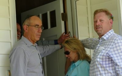 Key donors (from right) Brian Hudes, Molly Cooper, Joel Hoffman and Scott Cooper hold the mezuzah during its blessing.