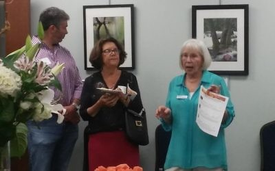 Artist Margery Diamond (right), speaking at the opening of her MACoM exhibit, says her latest camera is a Fujifilm mirrorless digital camera, but great photography is possible even with smartphones.