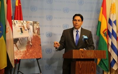 Danny Danon, Israel's ambassador to the United Nations, presents a photo Monday, July 24, of the bloody aftermath of the killing of three Israelis at their home in Halamish three days earlier.