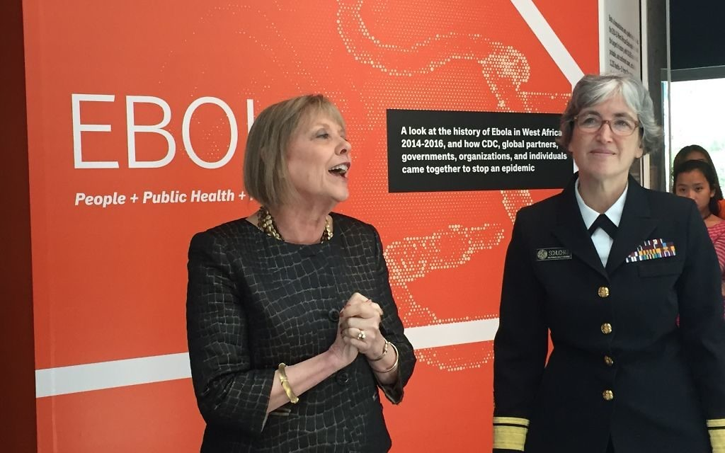 Acting CDC Director Anne Schuchat (right) and Museum Director Judy Gantt welcome guests to the agency's Ebola exhibit.