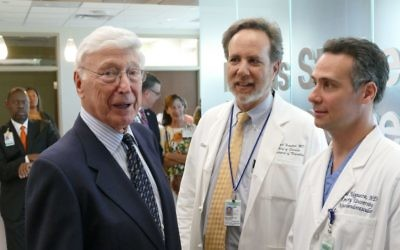 Bernie Marcus speaks with Michael Frankel (center), the chief of neurology and medical director of the Marcus Stroke & Neuroscience Center, and Raul Nogueira, the director of the center's neuroendovascular division.