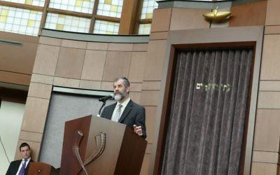 Beth Jacob President Josh Joel listens to Rabbi Ilan Feldman's speech.