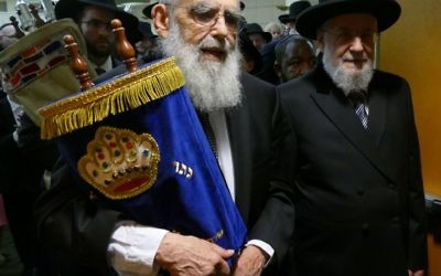 Accompanied by Rabbi Israel Meir Rau, Rabbi Emanuel Feldman carries one of Beth Jacob's Torahs from Heritage Hall to the new sanctuary.