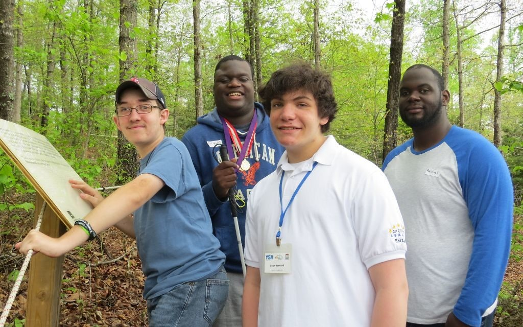 Evan Barnard helps visually impaired students make their way along the Whispering Woods Braille Trail in Buford during Global Youth Service Day.