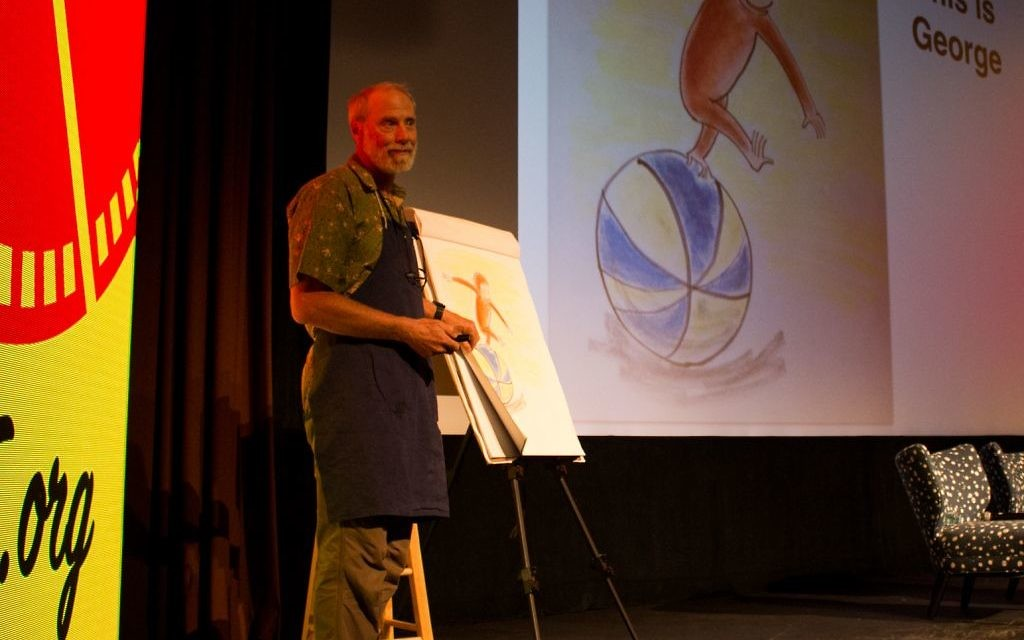 """Nat Scrimshaw talks about Curious George while drawing the famous monkey in the style of Hans Rey at the AJFF Selects screening of """"Monkey Business."""" (Photo by Tabitha Schwartz for the AJFF)"""