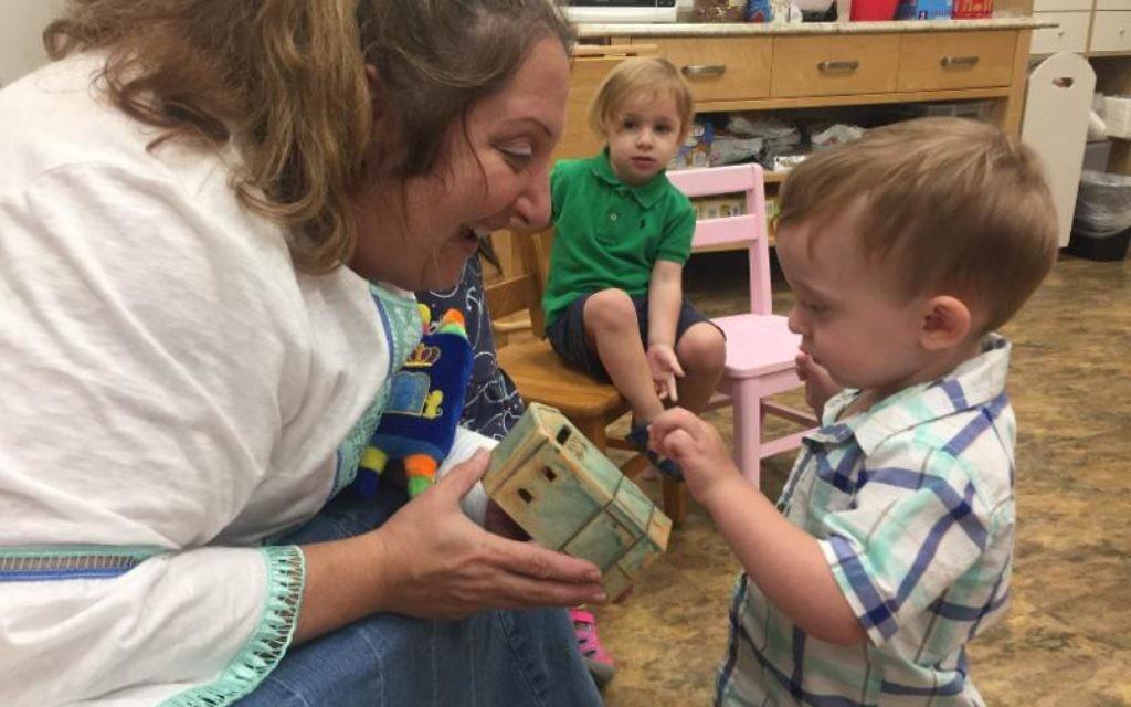 Morah Carol Epstein works with one of her preschoolers.