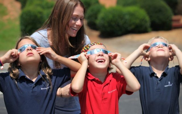 The scene in the early afternoon at the Epstein School is typical of schools and workplaces around metro Atlanta on Aug. 21: eyes shielded by special glasses, staring at the mostly eclipsed sun.