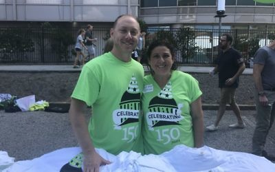 Photo by Rachel Fayne Congregation volunteers Mitch and Mia Spolan offer 150th birthday T-shirts to party attendees.