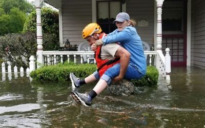 A Texas National Guardsman carries a resident from her flooded home following Hurricane Harvey in Houston. (Photo: U.S. Department of Defense)