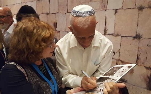 Edie Barr gets an autograph from Haim Oshri, one of three Israeli paratroopers from the famous David Rubinger photo at the Kotel in 1967.