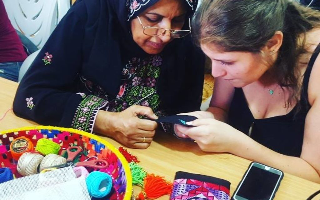 A Bedouin woman teaches embroidery to a Fashionating Israel participant.