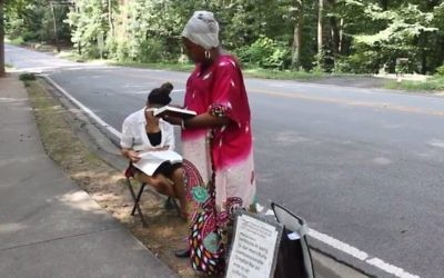 """Maverine """"Mercy"""" Henry sings outside Congregation Beth Tefillah on Saturday, Aug. 12. (Screen grab from Sandy Springs Reporter writer Dyana Bagby's YouTube video, https://youtu.be/2dYSJooleN8)"""