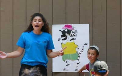 Israeli counselor Sapir Beresi leads campers in the Marcus JCC's Hebrew immersion day camp program in a game in which they must put articles of clothing on a zebra and say the items' names in Hebrew.