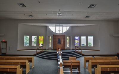 Four of the eight windows flanking the ark at Congregation Beth Tefillah now have stained-glass designs, while the other four windows await donors.